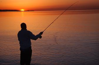 Fly fishing for striped bass in Long Island Sound at Compo Beach in Westport Connecticut at sunrise
